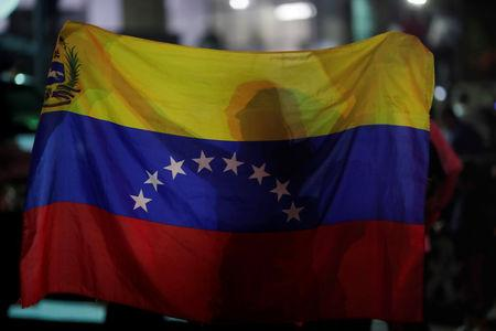A woman holds a Venezuelan flag while participating in a candlelight vigil held for victims of recent violence in Caracas
