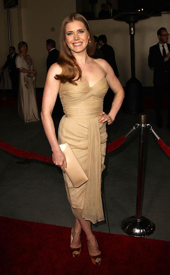 """Following in Jennifer's footsteps at the DGAs was fellow Oscar nominee Amy Adams (""""The Fighter""""), who popped a pose in a strapless, nude number. A matching clutch, burnt orange peep-toes, hoop earrings, and a bright smile completed the actress' lovely look. Frederick M. Brown/<a href=""""http://www.gettyimages.com/"""" target=""""new"""">GettyImages.com</a> - January 29, 2011"""