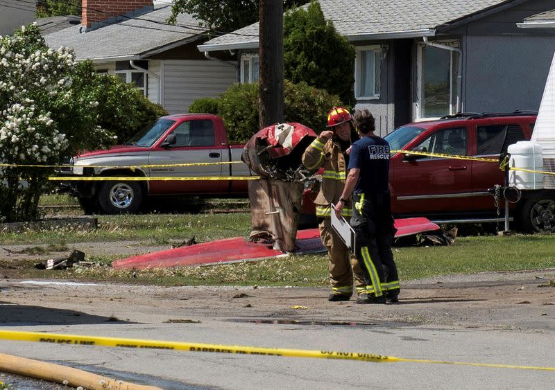 Fire officials talk in front of the tail wreckage from a Royal Canadian Air Force Snowbirds jet in Kamloops