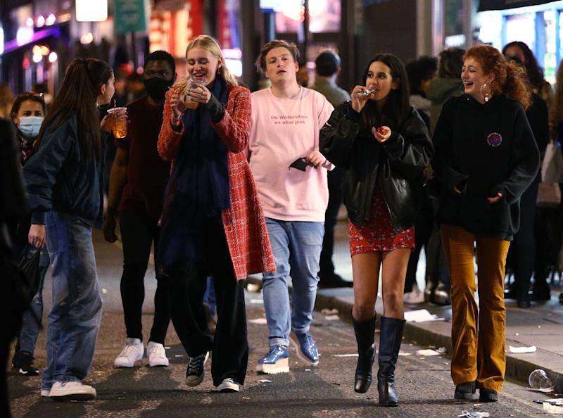 Revellers finish their drinks in the street after 10pm closing in London's Soho (PA)
