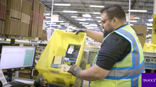 An Amazon fulfillment center worker getting ready to package a customer's order. Source: Yahoo Finance