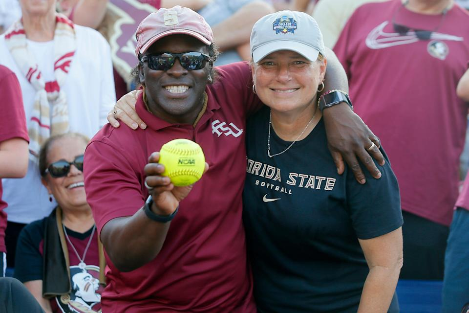 Karl and Sara Mason pose with the home run ball their daughter Elizabeth Mason hit during the second game of the Women's College World Series championship series between the University of Oklahoma Sooners (OU) and Florida State University at the USA Softball Hall of Fame Stadium in Oklahoma City, Wednesday, June 9, 2021.