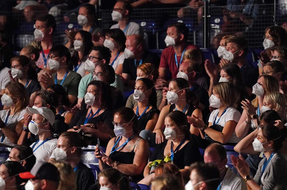 LEIPZIG, GERMANY - AUGUST 22: Participants wearing FFP2 protective face masks watch singer Tim Bendzko perform in the RESTART-19 Covid transmission risk assessment study in a concert setting at an indoor arena during the coronavirus pandemic on August 22, 2020 in Leipzig, Germany. The study, organized by the University Hospital of Halle (Saale), simulates a live concert venue with several thousand audience members in three different scenarios in order to develop risk reduction measures for large events. Participants wear tracer devices to track their movements and sensors measure aerosol currents in the arena. All participants had to undergo a Covid-19 test within the last 48 hours and test negative in order to take part.  (Photo by Sean Gallup/Getty Images)