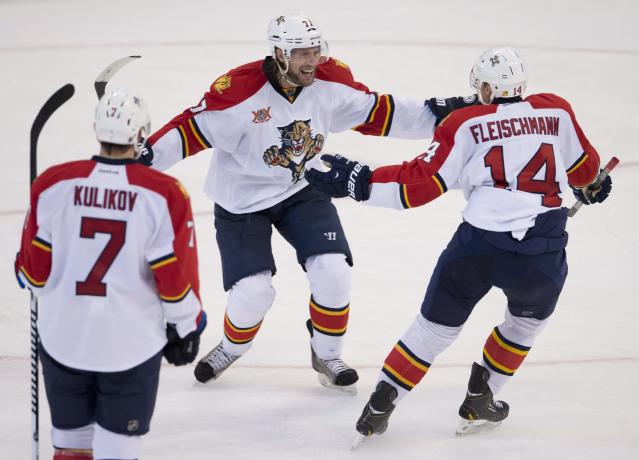 Florida Panthers defenseman Tom Gilbert, center, celebrates his game-winning goal with teammates Tomas Fleischmann, right, and Dmitry Kulikov, left, during third-period NHL hockey game action on Thursday, Dec. 19, 2013, in Ottawa, Ontario. The Panthers won 4-2. (AP Photo/The Canadian Press, Adrian Wyld)