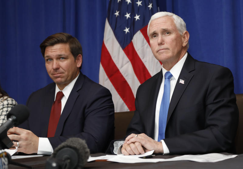 Vice President Mike Pence, right, and Florida Gov. Ron DeSantis take questions during a Florida Coronavirus Response Meeting, at the West Palm Beach International Airport, Friday, Feb. 28, 2020, in West Palm Beach, Fla. (AP Photo/Terry Renna)