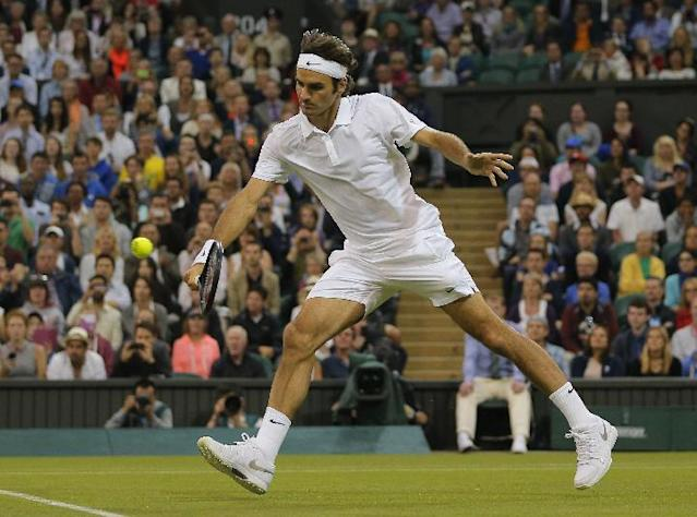 Roger Federer of Switzerland plays a return to Gilles Muller of Luxembourg plays a return to during their match at the All England Lawn Tennis Championships in Wimbledon, London, Thursday, June 26, 2014. (AP Photo/Pavel Golovkin)