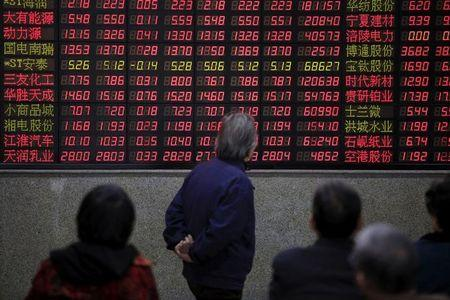 FILE PHOTO - Investors look at an electronic board showing stock information at a brokerage house in Shanghai, China, March 7, 2016. REUTERS/Aly Song/File Photo