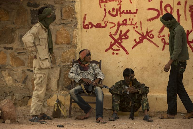 FILE - In this Friday, July 26, 2013 file photo, rebels from the National Movement for the Liberation of the Azawad (NMLA) stand guard outside the former governor's office, in Kidal, Mali. Mali's new president-elect Ibrahim Boubacar Keita, whose rival conceded defeat Monday, Aug. 12, a day after the vote, now faces the challenge of finding a resolution to the simmering separatist rebellion in the country's north. Based on his recent campaign visit to the rebel's stronghold, during which the NMLA tried to block his plane from landing, and then hurled stones at it while parked, the path to reconciliation is not likely to be an easy.(AP Photo/Rebecca Blackwell, File)