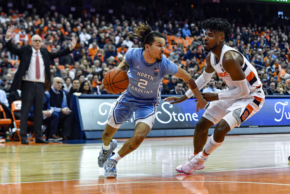 North Carolina guard Cole Anthony, left, is defended by Syracuse forward Quincy Guerrier during the second half of an NCAA college basketball game in Syracuse, N.Y., Saturday, Feb. 29, 2020. North Carolina defeated Syracuse 92-79. (AP Photo/Adrian Kraus)