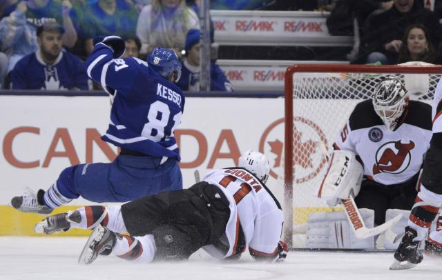 Toronto Maple Leafs' Phil Kessel is hauled down by New Jersey Devils' Stephen Gionta as he scores on goalie Cory Schneider during the third period of an NHL hockey game, Friday, Nov. 8, 2013 in Toronto. (AP Photo/The Canadian Press, Frank Gunn)