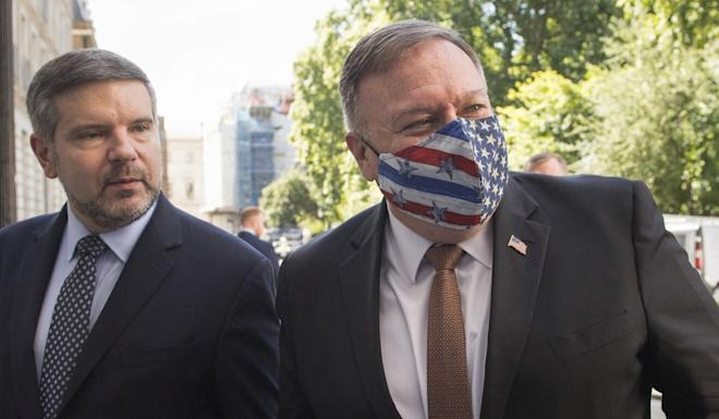 A masked Mike Pompeo with Alan Mendoza from the Henry Jackson Society think tank, which hosted a meeting between the Secretary of State and British politicians. Photo: AP