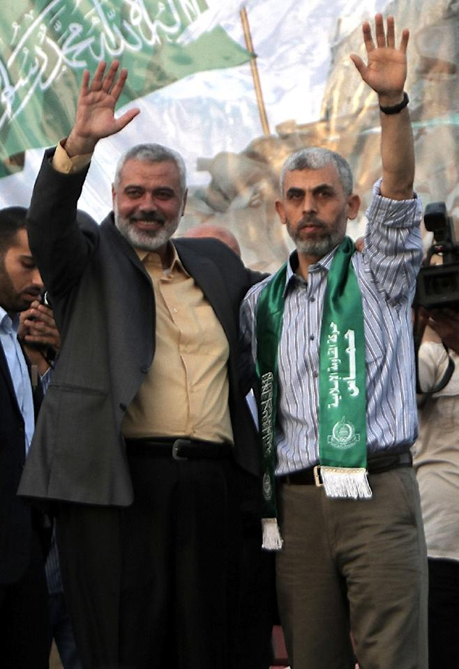 Hamas official Ismail Haniya (left) and freed Palestinian prisoner Yahya Sinwar -- a founder of Hamas' military wing -- wave to supporters during a 2011 rally to celebrate the release of hundreds of prisoners (AFP Photo/SAID KHATIB)