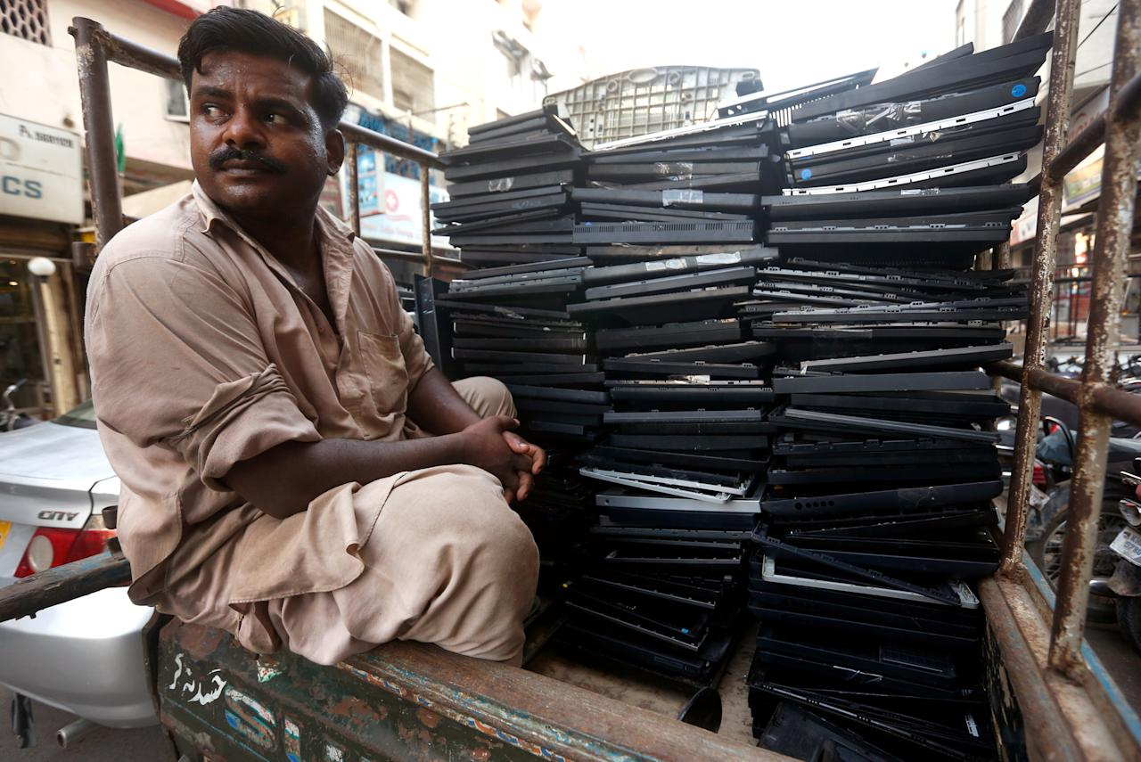 A man sits on back of a van with pile of discarded computer screen frames to be recycled, while heading to workshop in Karachi, Pakistan October 17, 2017. REUTERS/Akhtar Soomro