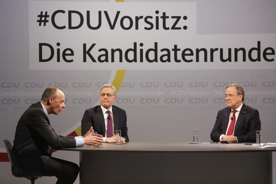 FILE - In this Dec. 14, 2020 file photo, the three candidates for the chairmanship of the Christian Democratic Union party, CDU, Friedrich Merz, left, Norbert Roettgen, center, and Armin Laschet, right, take part in a discussion at the party's headquarters in Berlin. German Chancellor Angela Merkel's center-right party, the Christian Democratic Union, CDU, is choosing a new leader on the weekend Saturday Jan. 16 and Sunday Jan. 17, 2021, a decision that will help determine who succeeds Merkel at the helm of the European Union's biggest economy after a 16-year reign.Background slogan reads: 'CDU Chairmanship: The candidate round'. (AP Photo/Markus Schreiber, File)