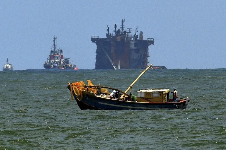 A Sri Lankan fishing boat operates against the backdrop of the MV X-Press Pearl, which lies partially submerged in shallow seas off Colombo