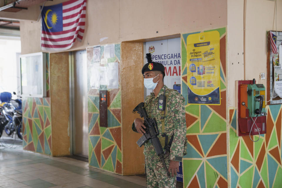 An armed soldier stands guard at the entrance of a high density residential area placed under the enhanced movement control order (EMCO) due to drastic increase in the number of COVID-19 cases recorded at Sentul in Kuala Lumpur, Malaysia, Saturday, July 3, 2021. Malaysia starts further tighten movement curbs and imposes a curfew in most areas in its richest state Selangor and parts of Kuala Lumpur, where coronavirus cases remain high despite a national lockdown last month. (AP Photo/Vincent Thian)