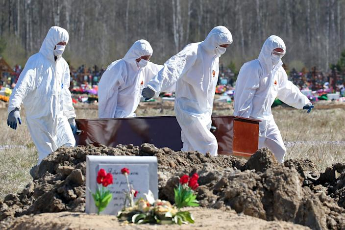 Workers in protective gear bury coronavirus victims in the Leningrad region of Russia on May 6, 2020.