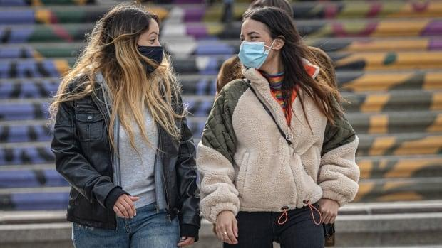A pair in masks walks in downtown Ottawa in March 2021.