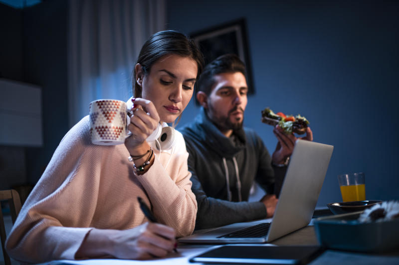 Young man and woman working from the comfort of their home at night. A woman is holding a cup of hot beverage while a man is eating a sandwich.