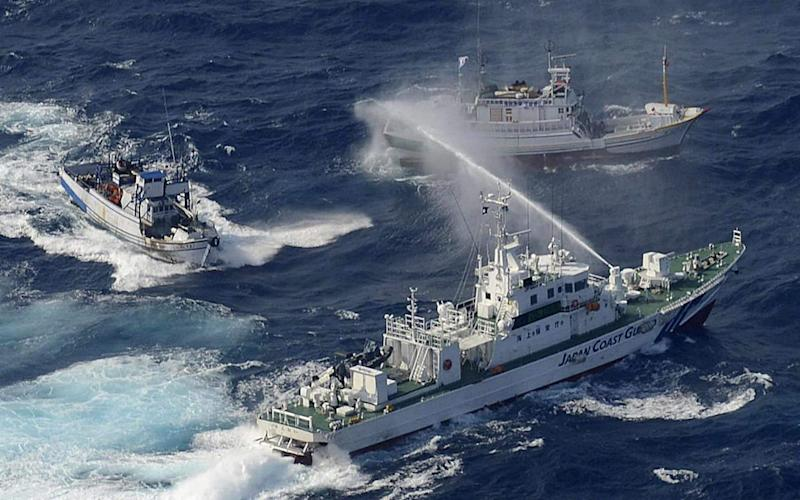 A Japanese Coast Guard boat sprays Taiwanese fishing boats with water in the disputed territory of the Senkaku islands - YOMIURI SHIMBUN/AFP