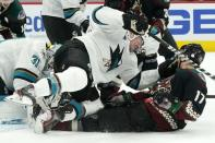 San Jose Sharks defenseman Marc-Edouard Vlasic, middle, knocks Arizona Coyotes center Tyler Pitlick (17) to the ice as Sharks goaltender Martin Jones (31) makes a save during the third period of an NHL hockey game Thursday, Jan. 14, 2021, in Glendale, Ariz. (AP Photo/Ross D. Franklin)
