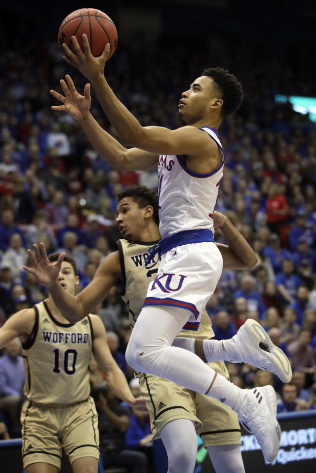 Kansas guard Devon Dotson (11) drives past Wofford forward Keve Aluma, back, during the first half of an NCAA college basketball game in Lawrence, Kan., Tuesday, Dec. 4, 2018. (AP Photo/Orlin Wagner)