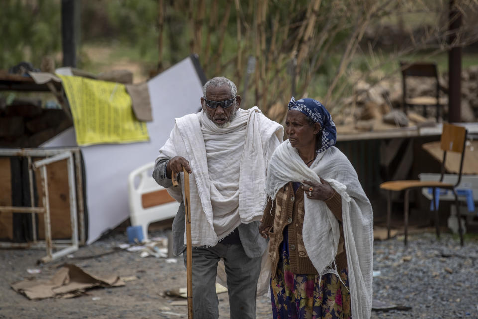 A woman leads a blind man to a visiting doctor, past destroyed furniture and other items in the driveway of a hospital which was damaged and looted by Eritrean soldiers who used it as a base, according to witnesses, in Hawzen, in the Tigray region of northern Ethiopia, on Friday, May 7, 2021. The battle for Hawzen is part of a larger war in Tigray between the Ethiopian government and the Tigrayan rebels that has led to the flight of more than 2 million of the region's 6 million people. (AP Photo/Ben Curtis)