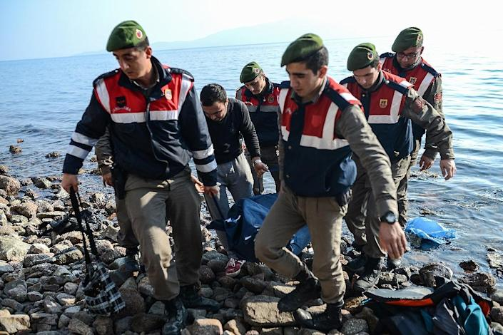 Turkish gendarmes carry the body of a migrant on a beach in Canakkale's Bademli district on January 30, 2016 (AFP Photo/Ozan Kose)