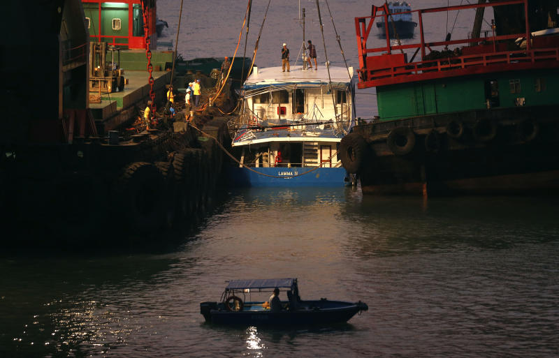 Workers check on a salvaged boat which sank previous night after colliding with a ferry near Lamma Island, off the southwestern coast of Hong Kong Island Tuesday, Oct. 2, 2012. The boat packed with revelers on a long holiday weekend sank, killing nearly 40 people and injuring dozens, authorities said. (AP Photo/Kin Cheung)