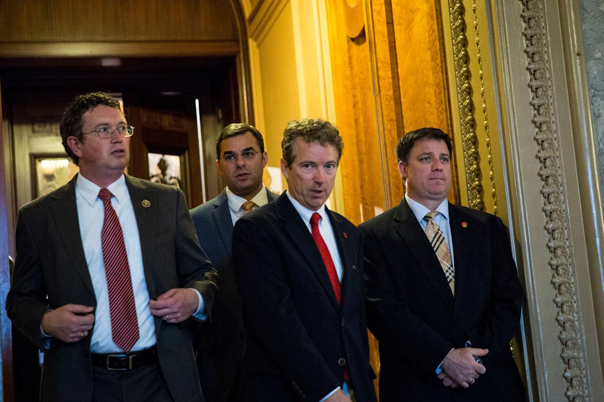 Rep. Thomas Massie (R-Ky.), left, and Sen. Rand Paul (R-Ky.), center, exit the Senate floor after Paul spoke about surveillance legislation on Capitol Hill on May 31, 2015.