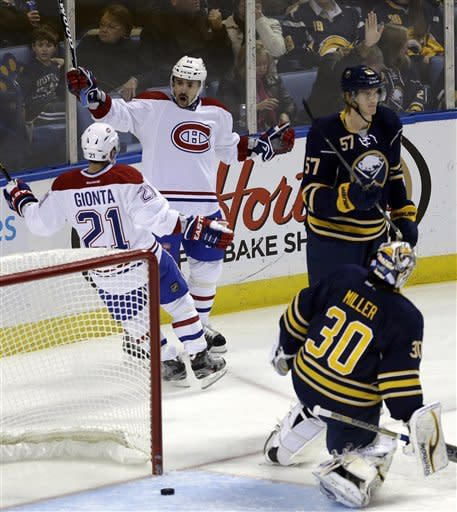 Montreal Canadiens' Tomas Plekanec (14), of the Czech Republic, celebrates his goal with Brian Gionta (21) on Buffalo Sabres' Ryan Miller (30), as Sabres' Tyler Myers (57) looks away during the first period of an NHL hockey game in Buffalo, N.Y., Thursday, Feb. 7, 2013. (AP Photo/David Duprey)