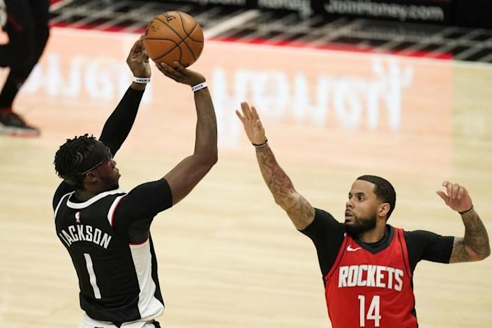 Los Angeles Clippers guard Reggie Jackson, left, shoots as Houston Rockets guard D.J. Augustin defends during the second half of an NBA basketball game Friday, April 9, 2021, in Los Angeles. The Clippers won 126-109. (AP Photo/Mark J. Terrill)