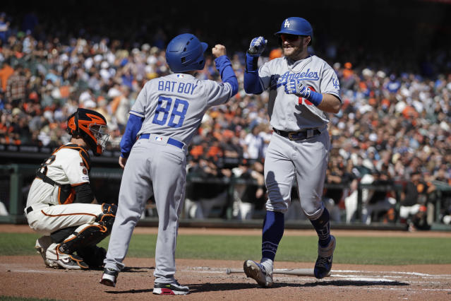 Los Angeles Dodgers' Max Muncy, right, celebrates with bat boy Champ Pederson after hitting a home run off San Francisco Giants' Logan Webb in the sixth inning of a baseball game Saturday, Sept 28, 2019, in San Francisco. (AP Photo/Ben Margot)