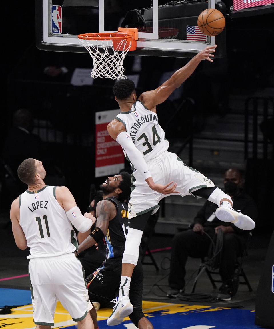 Milwaukee Bucks forward Giannis Antetokounmpo (34) blocks a shot by Brooklyn Nets guard Kyrie Irving (11) during the first half Game 2 of an NBA basketball second-round playoff series, Monday, June 7, 2021, in New York. Milwaukee Bucks center Brook Lopez (11) looks on. (AP Photo/Kathy Willens)