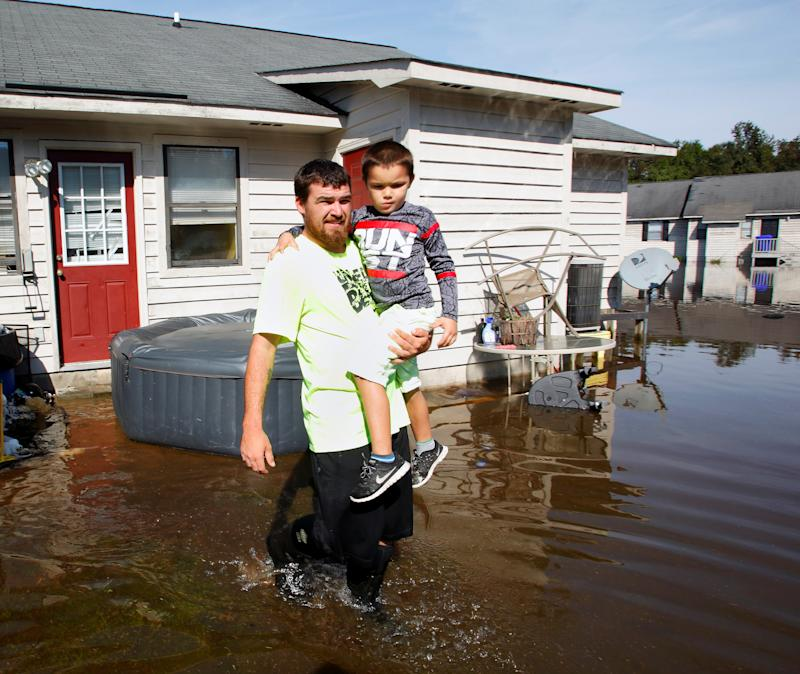 A man carries his son through flood waters surrounding their Greenville, North Carolina, home on Oct. 14, 2016, in the aftermath of Hurricane Matthew.