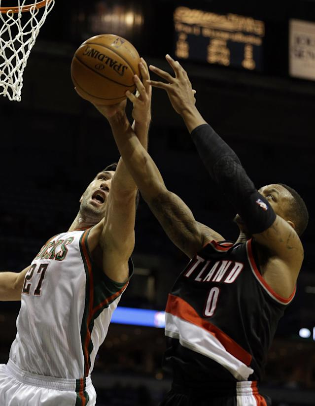 Milwaukee Bucks' Zaza Pachulia, left, reaches for a rebound against Portland Trail Blazers' Damian Lillard, right, during the second half of an NBA basketball game Wednesday, Nov. 20, 2013, in Milwaukee. (AP Photo/Jeffrey Phelps)