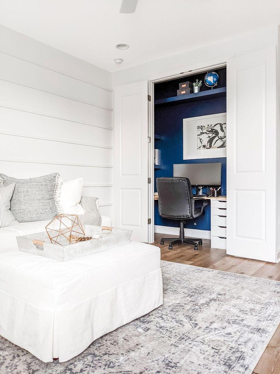 <p>Spruce up an all-white bedroom by weaving a pop of color, like a rich navy, into your closet office setup. Pull the look together with a statement piece of art. </p>