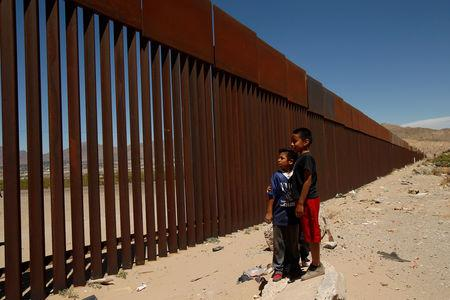FILE PHOTO: Children stand by a new section of the border wall on the U.S.-Mexico border in this picture taken from Anapra neighborhood in Ciudad Juarez, Mexico May 3, 2018. REUTERS/Jose Luis Gonzalez/File Photo