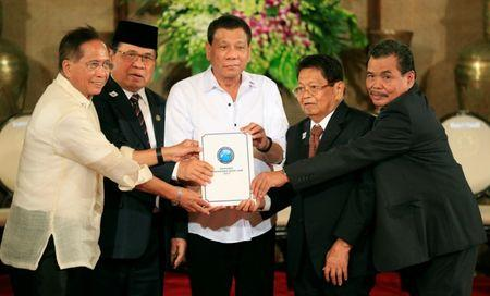 Philippine President Rodrigo Duterte (C) with Moro Islamic Liberation Front (MILF) chairperson Al Haj Murad Ebrahim (2nd from L), Jesus Dureza, Secretary of Peace Process, Ghazali Jaafar (2nd from R), MILF vice-chairman and Mohagher Iqbal, MILF peace panel chairman, hold a draft law of the Bangsamoro Basic Law (BBL) during a ceremony at the Malacanang presidential palace in metro Manila, Philippines July 17, 2017. REUTERS/Romeo Ranoco