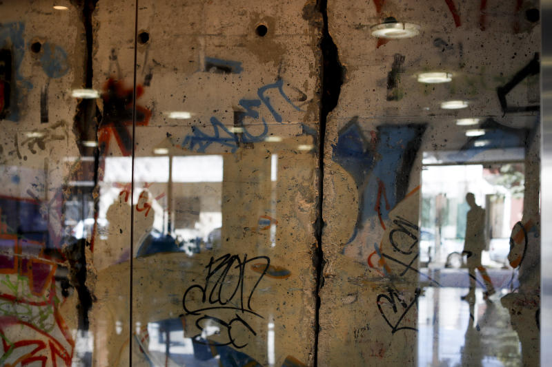 In this Thursday, Sept. 26, 2019 photo a man is reflected in a glass protecting a segment of the Berlin Wall at Editorial Perfil in Buenos Aires, Argentina. (AP Photo/Natacha Pisarenko)