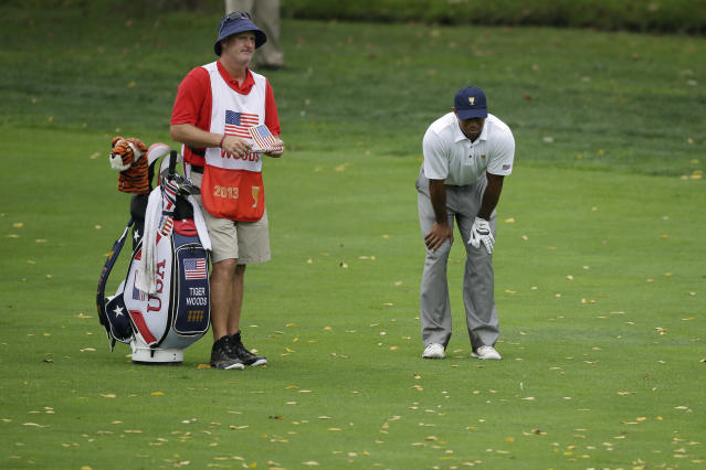 United States team player Tiger Woods, right, reacts after a shot on the 18th hole with caddie Joe LaCava during the single matches at the Presidents Cup golf tournament at Muirfield Village Golf Club Sunday, Oct. 6, 2013, in Dublin, Ohio. (AP Photo/Darron Cummings)