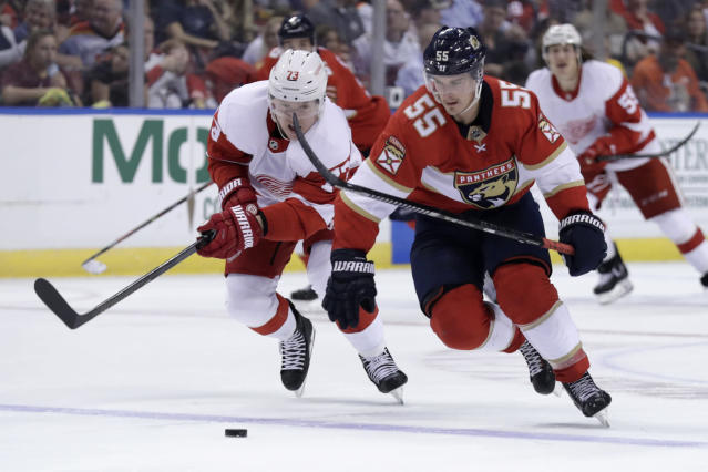 Detroit Red Wings left wing Adam Erne (73) and Florida Panthers center Noel Acciari (55) chase the puck during the second period of an NHL hockey game Saturday, Nov. 2, 2019, in Sunrise, Fla. (AP Photo/Lynne Sladky)