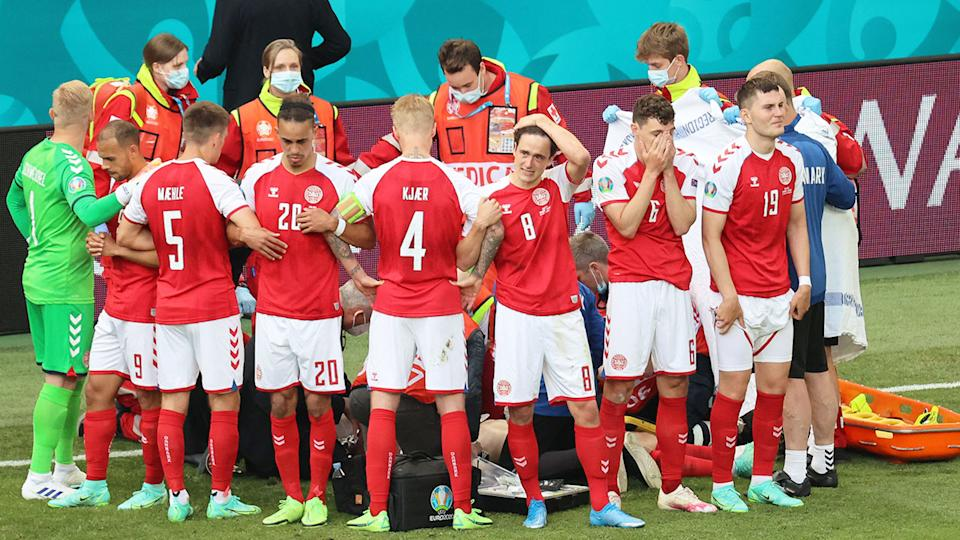 Devastated Denmark teammates are seen here after Christian Eriksen collapsed on the pitch.