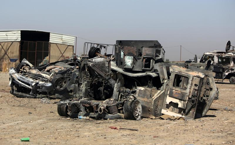 Burned and destroyed Iraq military vehicles on a road in the town of Samarra, on July 12, 2014