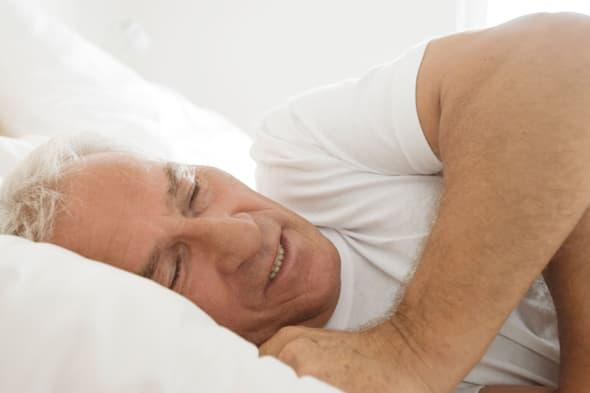 A0KB5X mature man sleeping in bed