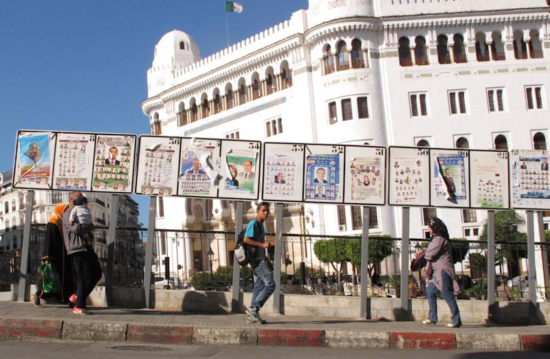 FILE - In this April 30, 2012 file photo, Algerians walk by posters for election lists displayed in front of the main post office in downtown Algiers. Two years after an itinerant Tunisian fruitseller set himself on fire to protest government injustice and ignited uprisings across the Middle East, the three nations of the Maghreb _ Algeria, Tunisia and Morocco_ have taken wildly different paths, from wholesale political change in Tunisia, to business as usual in oil-rich Algeria. (AP Photo/Paul Schemm, File)