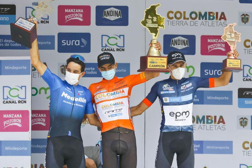 Cyclist Diego Camargo C celebrates on the podium  next to Oscar Sevilla L and Juan Pablo Suarez after winning the VueltaColombia in Medellin Colombia on November 22 2020 Photo by Joaquin Sarmiento  AFP Photo by JOAQUIN SARMIENTOAFP via Getty Images