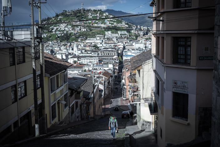 """A delivery man walks to a garage he rents in the center of Quito, Ecuador. Many delivery drivers do not own their motorcycles or garages and often rent, leaving them with less profit.<span class=""""copyright"""">Isadora Romero—Magnum Foundation</span>"""