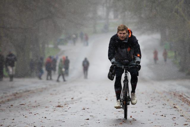 A man cycles through the snow in Greenwich Park, London
