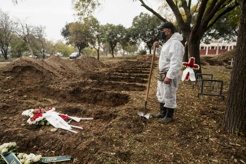 A worker stands over graves during a funeral ceremony for a person who died of COVID-19, in the northern city of Thessaloniki, Greece, Saturday, Dec. 5, 2020. Greece is on lockdown until Dec. 7 but government officials say it is too early to say when schools and businesses will reopen due to continued pressure on the state-run health service, with intensive care wards near capacity in parts of the country. (AP Photo/Giannis Papanikos)